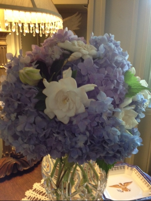 White gardenias and blue hydrangeas in a beautiful crystal vase